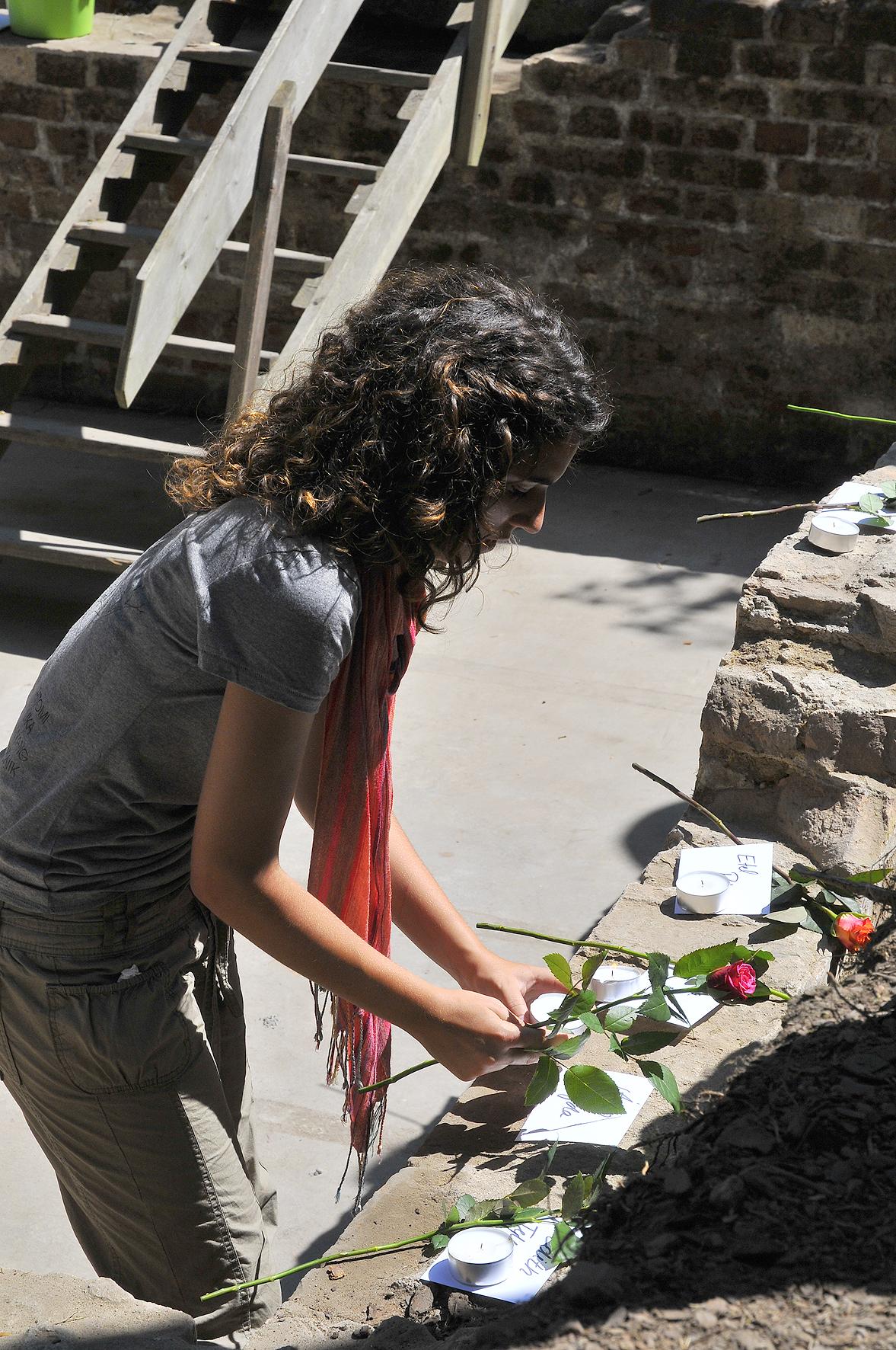 Im Rahmen eines work-and-study Camps gedenkt eine Teilnehmerin mit einer Rose dem Leid, das den Häftlingen in der KZ-Außenstelle Walldorf zugefügt wurde.