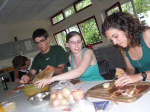 Während eines work-and-study Camps: Teilnehmerinnen und Teilnehmer bereiten gemeinsam das Essen zu.