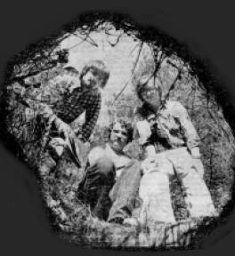 """Die drei Jugendlichen, Jossy, Gerd und Alex, die die Geschichte der KZ-Außenstelle 1972 wieder entdeckten. """"Opening to the past"""" betitelte ein amerikanischer Journalist dieses Foto für die Zeitung """"Stars and Stripes"""". 4. November 1978."""